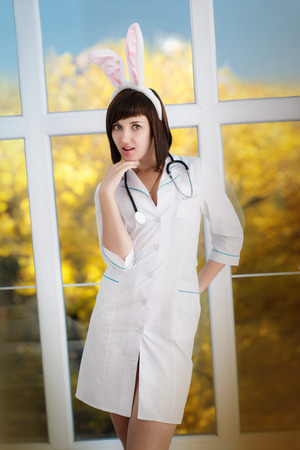 Sexy attractive nurse in a dressing gown with ears of rabbit Stock Photo