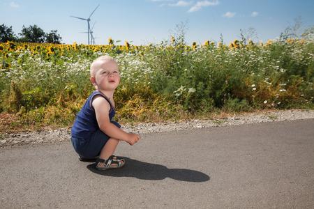 asphalt road: Child sits on asphalt road