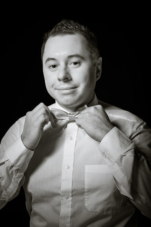 corrects: Man corrects a necktie Stock Photo