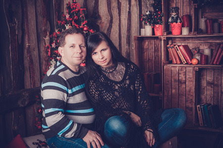 Loving couple smiling beside their christmas tree at home photo