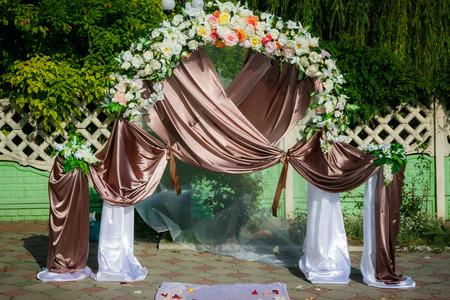 결혼식을 위해 공원에서 꽃 배열 결혼식 아치 밑의 통로