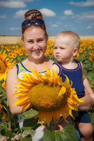 Mother and son having fun in the field of sunflowers photo