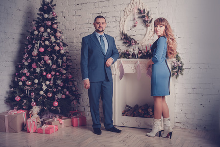 Man and woman in room with Christmas tree and fireplace photo