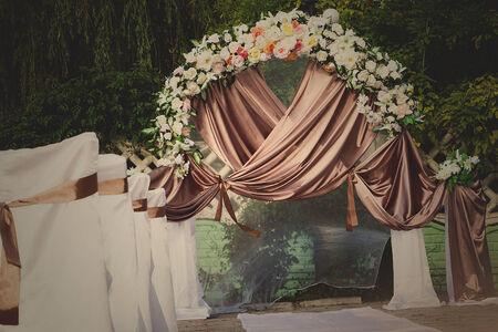 c�r�monie mariage: arche de mariage avec des fleurs dispos�es dans le parc pour une c�r�monie de mariage
