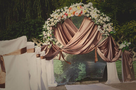 outdoor wedding: Wedding archway with flowers arranged in park for a wedding ceremony Stock Photo