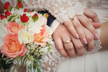 wedlock: Bride and grooms hands with wedding bouquet and rings