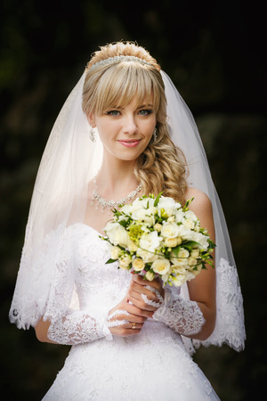 bouqet: Portrait of a beautiful blonde bride with wedding bouqet in the hands