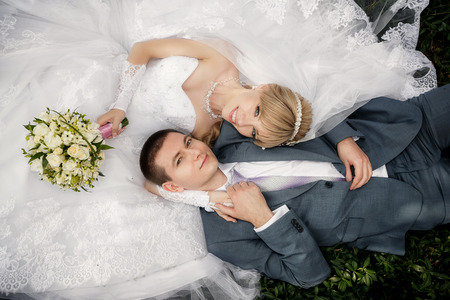 lying on grass: Happy bride and groom are lying on green grass