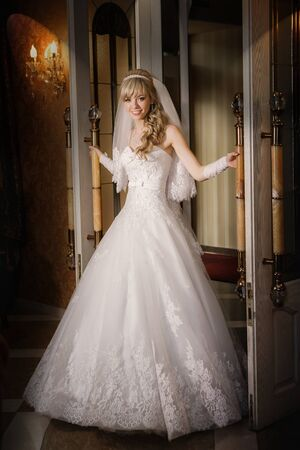 sexy bride: beautiful sexy bride blonde in a white dress is leaving the door Stock Photo