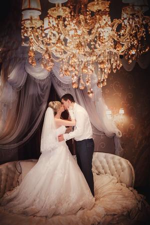 wedding couple: bride and groom is kissing in bedroom