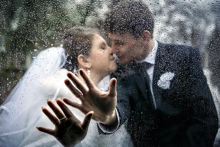 uomo sotto la pioggia: immagine delle mani di una sposa e uno sposo sulla finestra di automobile con gocce da una pioggia sullo sfondo un bacio dello sposo e la sposa