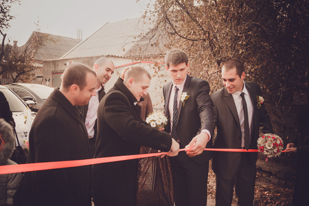 repayment: Groom with best man and groomsmen  go to the bride at wedding. Repayment of the bride. Russian custom.
