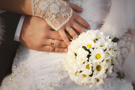 anillos boda: Bride and groom hands with wedding rings and bouquet of white chrysanthemums
