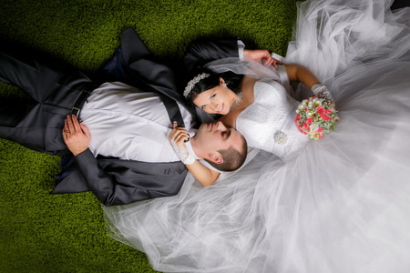 Smiling bride and groom lying on the grass-like carpet.