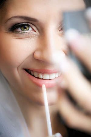 gloss: Make up process. The making of nude look for lips. Fresh and sparkling lips made by a lip gloss and professional lip brush. The finishing accent for every make up. Stock Photo