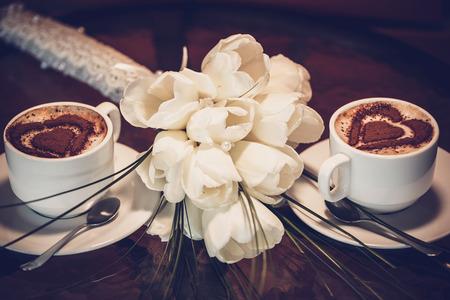 desayuno romantico: Dos tazas de caf� y blanco tulipanes