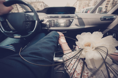bride and groom background: happy couple driving in the car