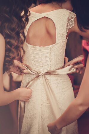 Bride is putting on her white wedding dress Stock Photo