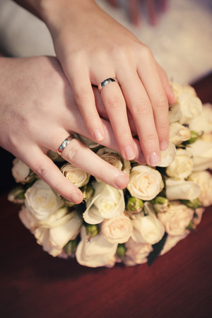 ramo de flores: Manos del novio y la novia con los anillos de bodas y un ramo de boda de las rosas