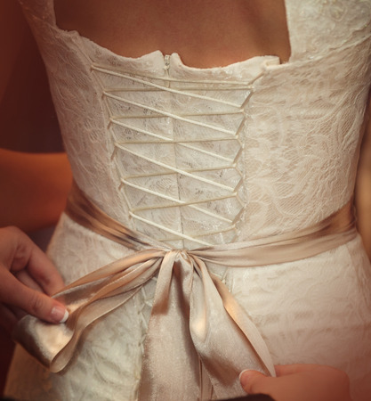 zip tie: Bride is putting on her white wedding dress Stock Photo