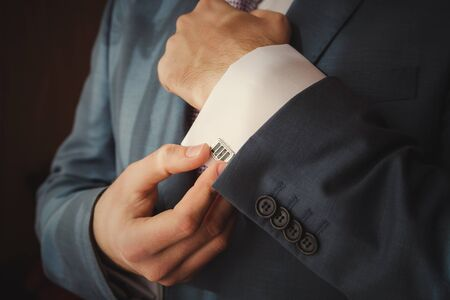 businesswear: groom putting on cuff-links as he gets dressed in formal wear close up
