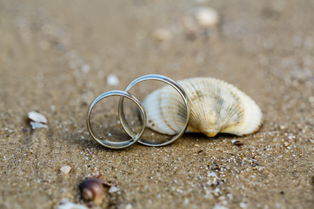 couple amoureux: Wedding ring and seashell on the sandy beach Banque d'images