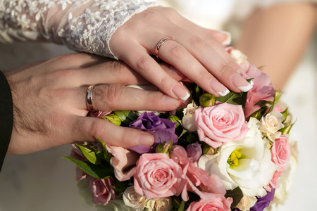 wedding rings: Hands of the groom and the bride with wedding rings and a wedding bouquet from roses