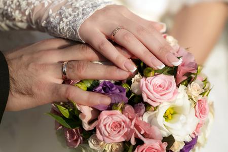 anillos de boda: Manos del novio y la novia con los anillos de bodas y un ramo de boda de las rosas