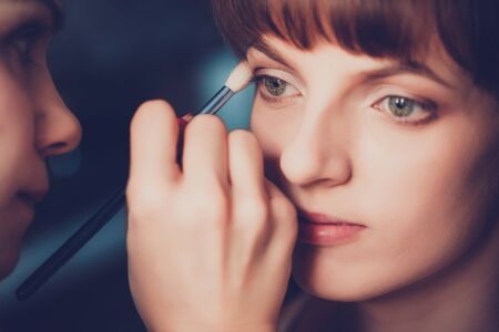 Young beautiful girl applying make-up by make-up artist close up photo