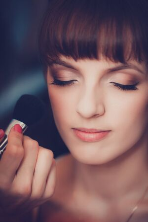 Young beautiful girl applying make-up by make-up artist close up Imagens