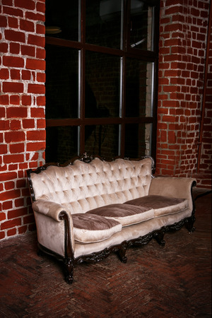 red sofa: Living room with beige sofa on the  red brick wall background