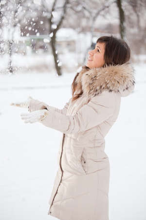 Girl is playing with snow in park photo