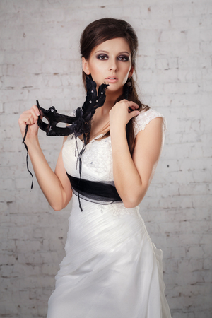 black mask: girl in a white dress with a black mask in studio Stock Photo