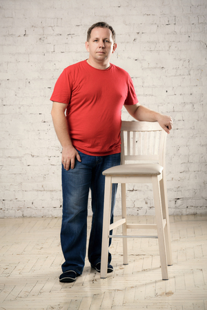 red tshirt: man in a red t-shirt stands near a chair in studio