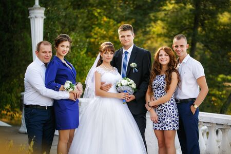 bridesmaids: portrait of newlywed couple with bridesmaids and groomsmen in green sunny park Stock Photo