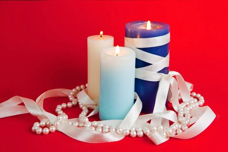 Three burning candles with a tape and a pearl beads on the red background Stock Photo
