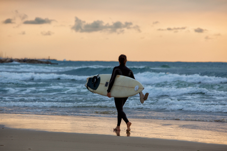 Sporty girl go to surfing. Woman in wetsuit and sunset or sunrise on ocean photo