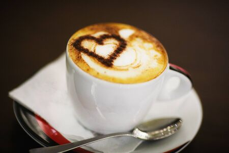 A cup of coffee with heart pattern in a white cups on wooden background. Love concept. Stock Photo