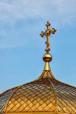 Gilded dome of orthodox Christian church shines on the blue sky background