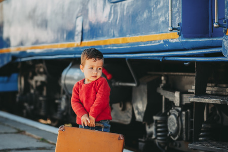 Adorable little kid boy dressed in red sweater on a railway station near train with retro old  brown suitcase. Ready for vacation. Young traveler on the platform.