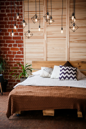 Simple bedroom with double bed, red brick wall and big window