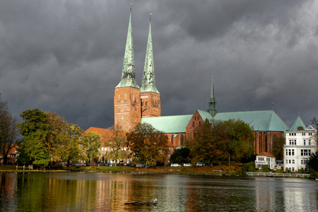 View of Lubeck Cathedral from Muhlenteich (Mill pond) in autumn, Germany. The cathedral was started in 1173 and consecrated in 1247.