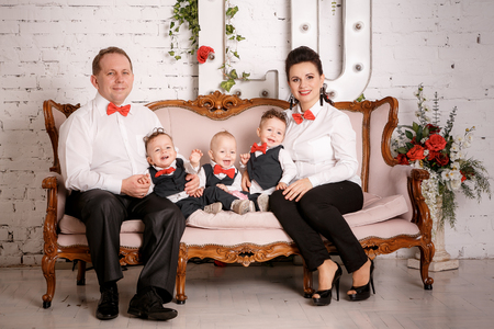 Big happy family: mother, father, triplets sons Stockfoto