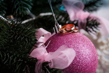 Wedding rings, pink Christmas ball, Christmas tree in the snow, for advertising, Stockfoto