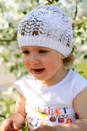 The child in flowers of an apple-tree Stock Photo