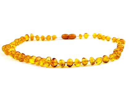 finesse: Closeup of an amber necklace on white background Stock Photo