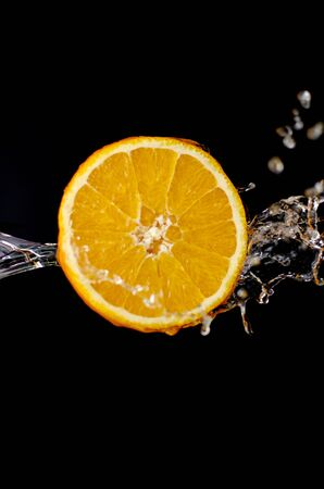 orange is dropped into water splash