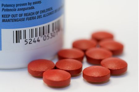 visible: group of red pills with visible warning label from bottle and altered barcode Stock Photo