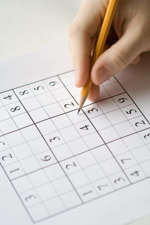 sudoku: sudoku puzzle and hand holding pencil