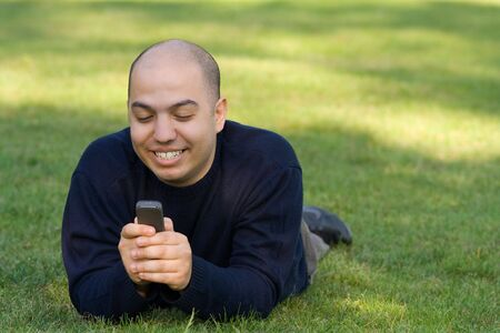 Young man lying on grass and messaging on the mobile phone photo